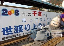大看板の前で年男をアピールする、水木しげるさんの漫画「ゲゲゲの鬼太郎」で人気の妖怪「ねずみ男」=10日、鳥取県境港市