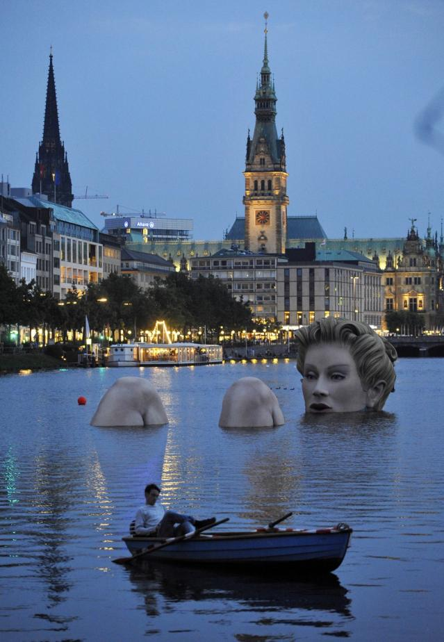 142973-man-in-a-rowing-boat-floats-near-a-mermaid-sculpture-created-by-oliver.jpg