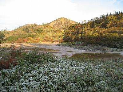 霜のおりた高谷池から火打山を見上げる
