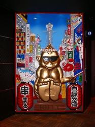 写真①=8階のエントランスにある「難波自己解放酒場串丸」の巨大看板
